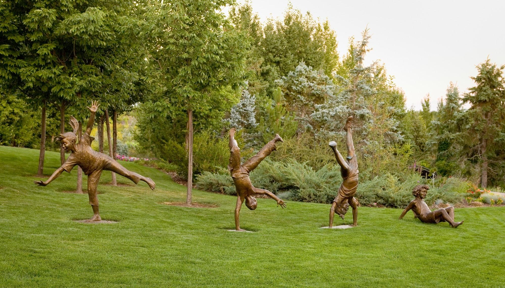 four bronze sculptures depict children cart-wheeling across a green field of grass.