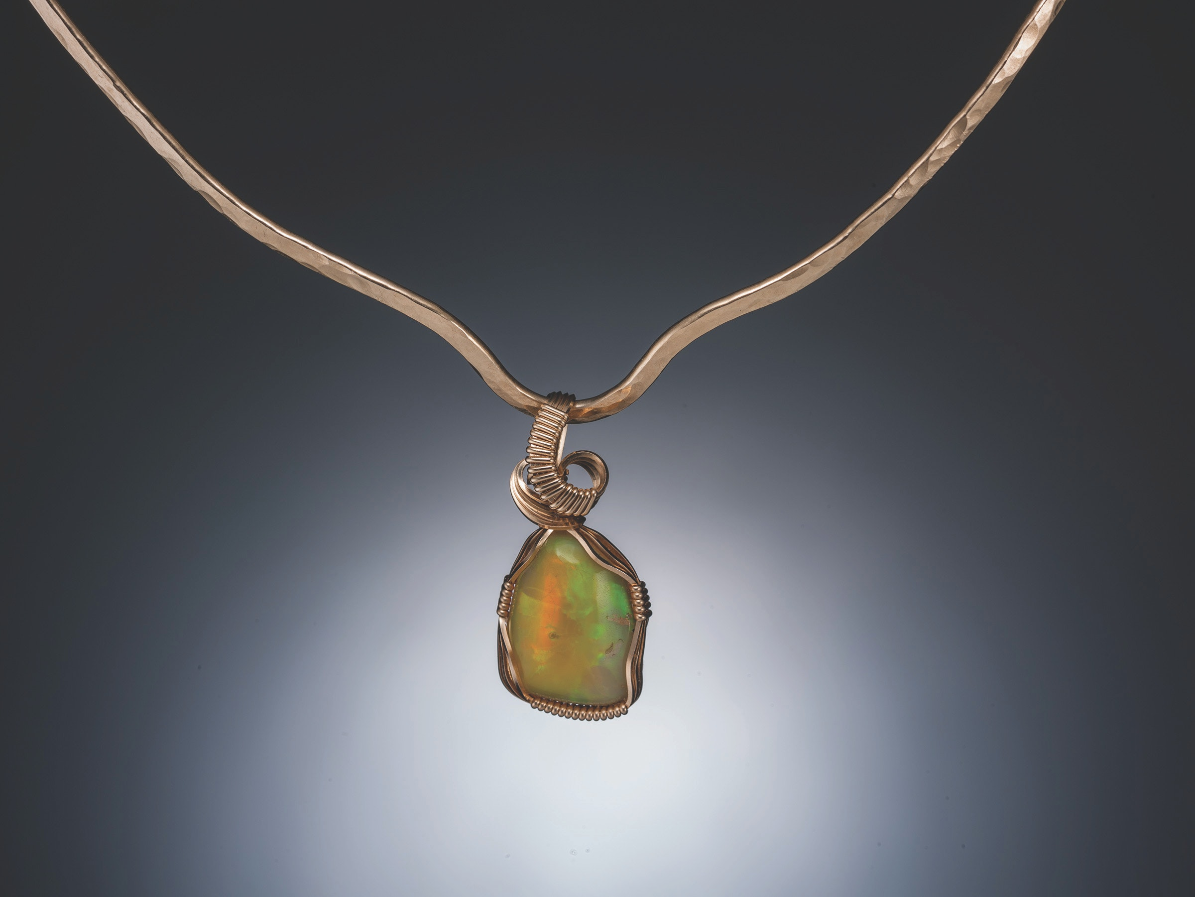 Close up of necklace with orange and green stone.